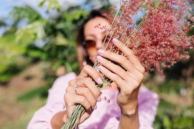 Портрет молодой кавказской загорелой женщины в романтическом розовом платье с круглыми серьгами, серебряным браслетом и солнцезащитными очками с полевыми цветами