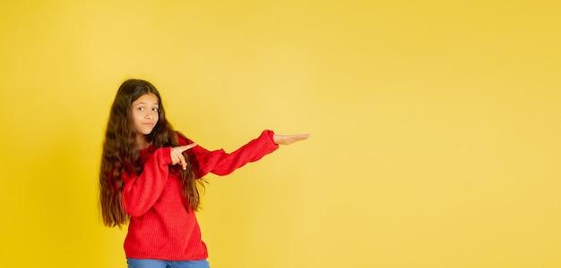 黄色のスタジオの背景に分離された明るい感情を持つ若い白人の十代の少女の肖像画