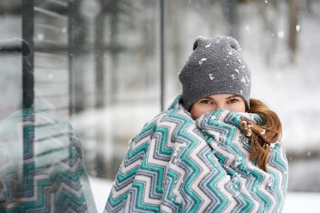 Портрет молодой кавказской женщины, закрывающей лицо клетчатыми фасадами во время снегопада