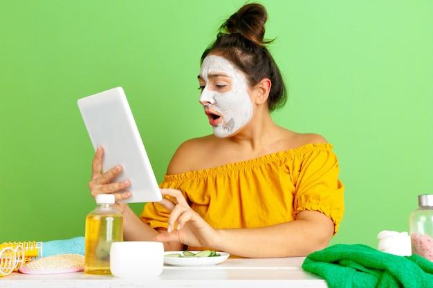 아름다움의 날, 피부와 헤어 케어 루틴에서 젊은 백인 여자의 초상화. 얼굴 마스크를 적용하는 동안 셀카, 동영상 블로그 또는 화상 통화를 만드는 여성 모델. selfcare, 자연의 아름다움과 화장품 개념.