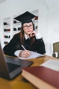 Портрет молодой кавказской женщины в очках, студент колледжа в выпускной форме, делая заметки