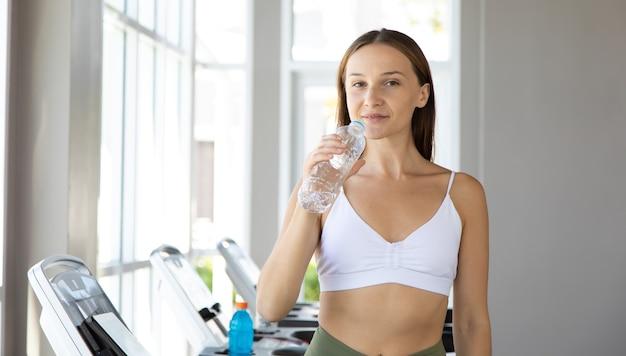 水のボトルを保持し、フィットネスジムで飲んでスポーツウェアの若い白人女性の肖像画。健康的なライフスタイルとスポーツの概念。