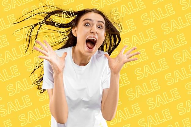 黄色の背景に若い白人女性の肖像画。悲鳴を上げ、ショックを受け、不思議に思い、驚いた。販売、ブラックフライデー、サイバーマンデー、金融、ビジネスの概念。オンラインショップと支払い請求書。