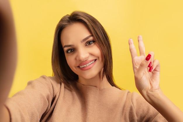 黄色のスタジオの背景に分離された明るい感情を持つ若い白人女性の肖像画