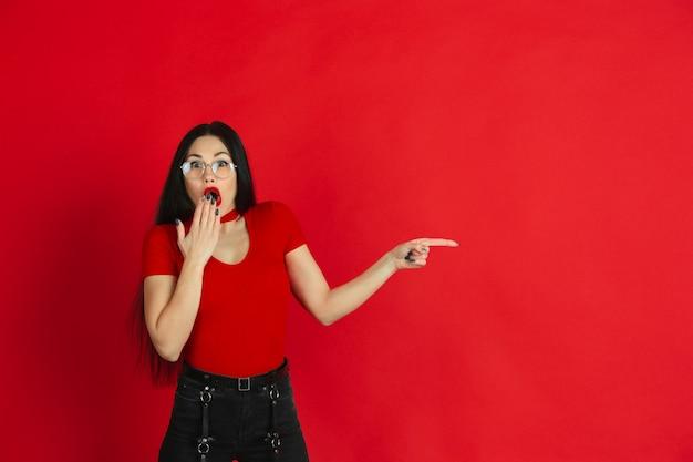 赤いスタジオの背景に明るい感情を持つ若い白人女性の肖像画