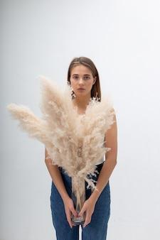 白い背景の上のパンパスグラスの花束を保持しているブルージーンズの長い髪の若い白人女性の肖像画。ドライフラワーとスタジオでポーズをとるきれいな女性