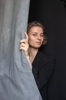 커튼을 들고 검은 정장 재킷에 포즈를 취하는 짧은 머리를 가진 젊은 백인 여자의 초상화. 예쁜 아가씨의 근접 촬영 샷입니다. 짧은 머리 매력적인 여성 스튜디오에서 포즈