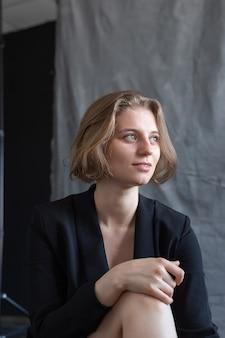 灰色の布の前に座って、黒いスーツのジャケットでポーズをとって短い髪の若い白人女性の肖像画。かわいい女の子の笑顔。スタジオでの短い髪の魅力的な女性のポーズ