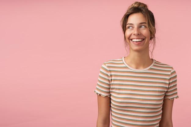 手を下にピンクの背景の上に立って、元気に脇を見ながら広く笑っているナチュラルメイクの若い魅力的なブルネットの女性の肖像画