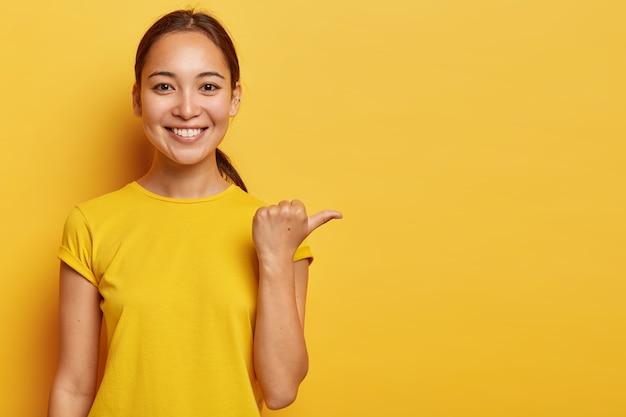 Портрет молодой жизнерадостной азиатской девушки показывает пальцем в сторону, счастливое выражение лица, демонстрирует место для рекламы, имеет приятный внешний вид, носит ярко-желтую одежду.