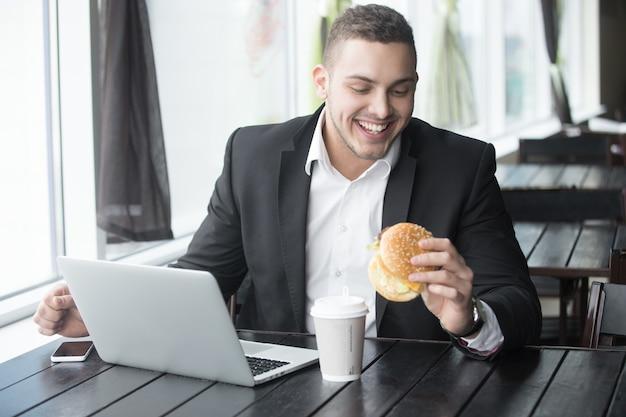 Портрет молодой жизнерадостный бизнесмен, едят гамбургер, работая в кафе