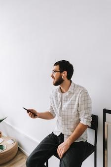 携帯電話を使用して眼鏡とイヤホンで若い陽気な白人男性の肖像画。