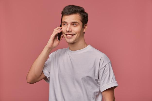 Портрет молодого веселого парня в пустой футболке, говорит по телефону и выглядит счастливым, стоит на розовом.