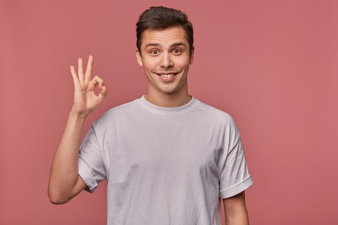 Портрет молодого веселого парня в пустой футболке, показывает хороший жест, стоит на розовом и широко улыбается.