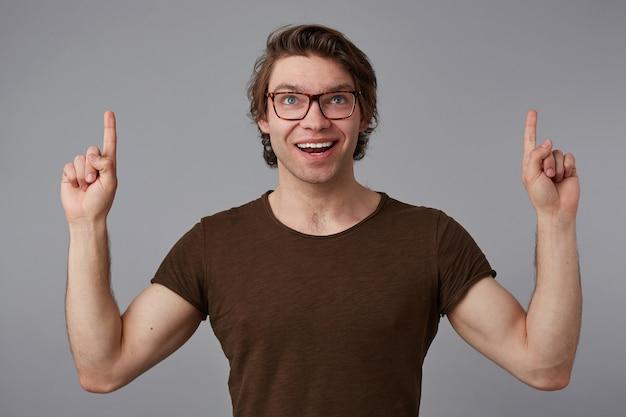 Портрет молодого веселого парня в очках, стоит на сером фоне с удивленным выражением лица, указывает пальцами на место для копирования над головой, смотрит в камеру и широко улыбается.