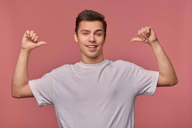 쾌활한 젊은 잘 생긴 남자의 초상화는 공백 t- 셔츠를 입고, 자신을 가리키며, 분홍색으로 넓게 웃고 있습니다.