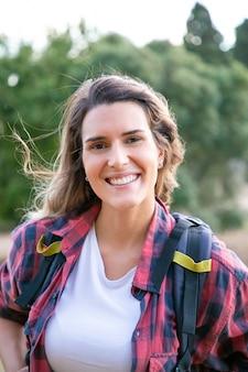 Портрет молодой веселой дамы позирует, улыбаясь. красивая кавказская женщина нося рюкзак, стоя и наслаждаясь природой. концепция туризма, приключений и летних каникул
