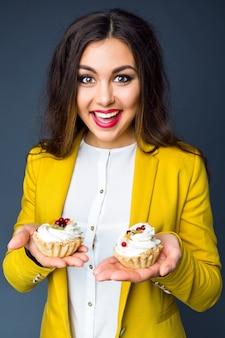 2つのおいしいケーキを保持している、笑顔で楽しい若い陽気なかなりブルネットの女性の肖像画。ポジティブな感情、明るい色。