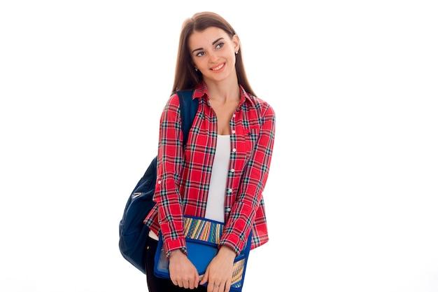 白い背景で隔離のノートブック用のバックパックとフォルダーを持つ若い陽気な学生の女の子の肖像画