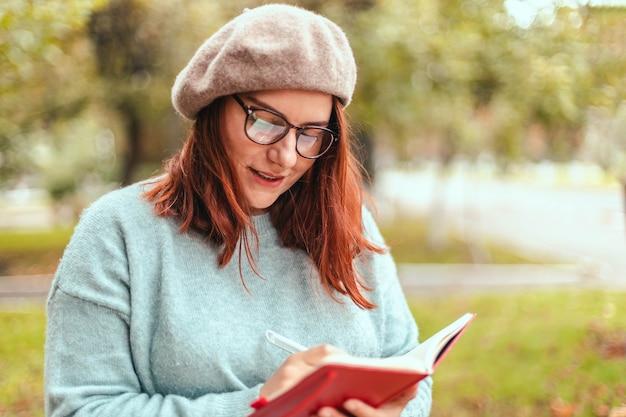 Портрет молодой веселой студентки, писать заметки в блокноте, сидя на открытом воздухе в природном парке