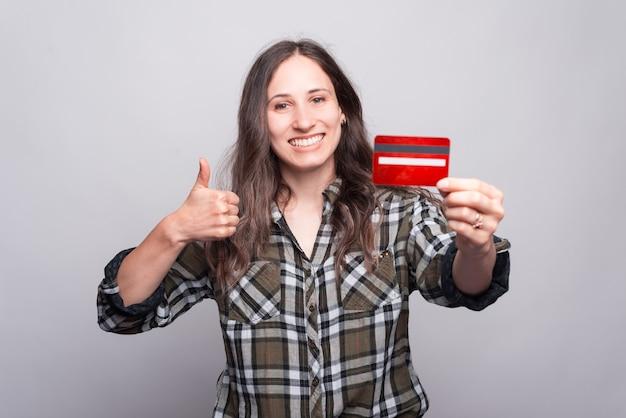 Портрет молодой жизнерадостной женщины показывая большой палец руки вверх и держа красную кредитную карту. с удовольствием покупаю онлайн