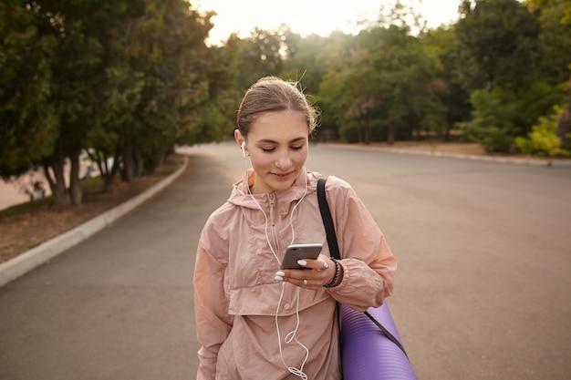 Портрет молодой веселой женщины гуляет после йоги в парке и болтает, держит смартфон в руке, слушает музыку в наушниках, смотрит на дисплей и улыбается.