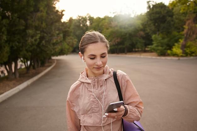 Портрет молодой веселой женщины, идущей после йоги в парке и болтающей, смотрит на смартфон в руке, слушая музыку в наушниках.