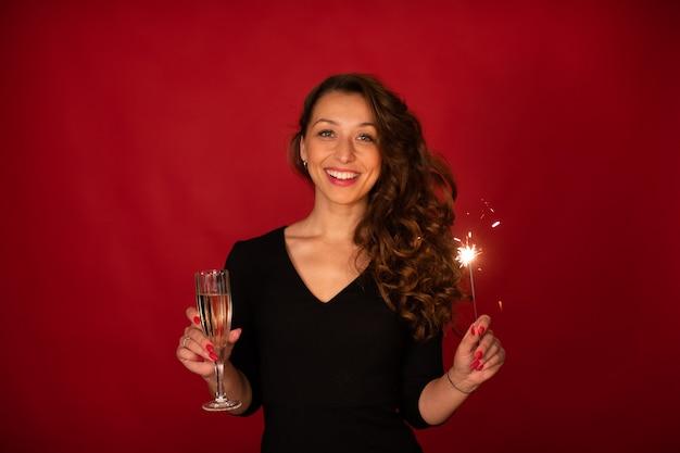 Портрет молодой веселой женщины с шампанским и бенгальским огнем