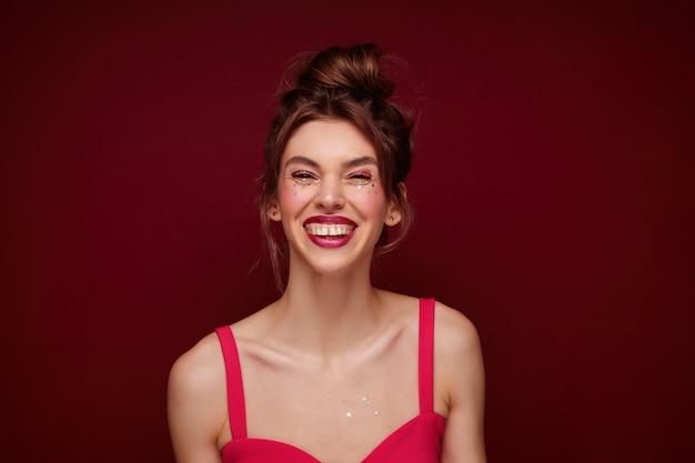 Claret 입술과 롤빵에 그녀의 갈색 머리를 입고 그녀의 얼굴에 작은 은색 별을 가진 젊은 쾌활한 여자의 초상화, 고립 된 매력적인 미소로 행복하게 찾고