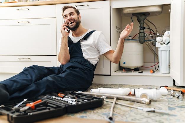 Портрет молодой веселый улыбающийся человек-сантехник работает в униформе в помещении, разговаривает по мобильному телефону.