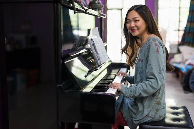 집 거실에서 피아노를 치는 젊은 중국 여성의 초상화. 미소 아시아 소녀는 음악을 만들기 위해 멜로디 노트 동안 카메라를 봐.