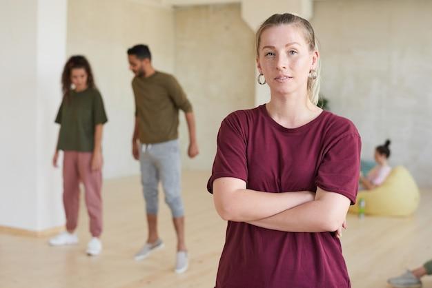 그녀의 팔으로 서있는 젊은 코치의 초상화가 넘어서 헬스 클럽에서 사람들을 훈련시키는 동안