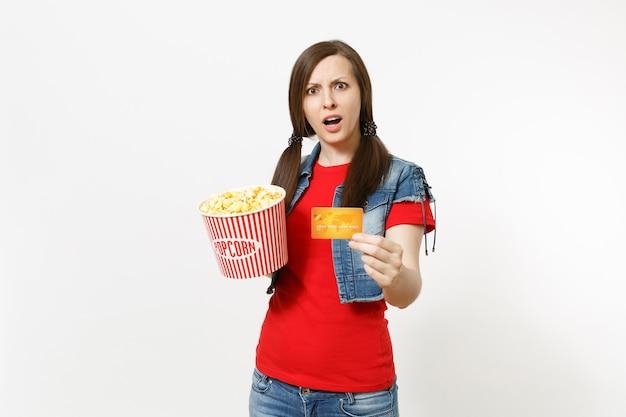 흰색 배경에 격리된 팝콘과 신용카드 양동이를 들고 영화 영화를 보는 캐주얼한 옷을 입은 젊은 관심 있는 매력적인 브루네트 여성의 초상화. 영화 개념의 감정.