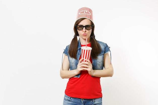 映画フィルムを見て、白い背景で隔離のソーダまたはコーラのプラスチックカップを保持している頭の上のポップコーンのバケツと3dメガネで若い心配するきれいな女性の肖像画。映画の感情。