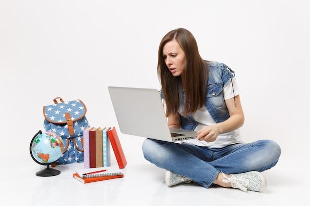 Портрет молодой обеспокоенной озадаченной студентки, держащей компьютер портативного компьютера, сидящей рядом с земным шаром, рюкзаком, изолированными школьными учебниками