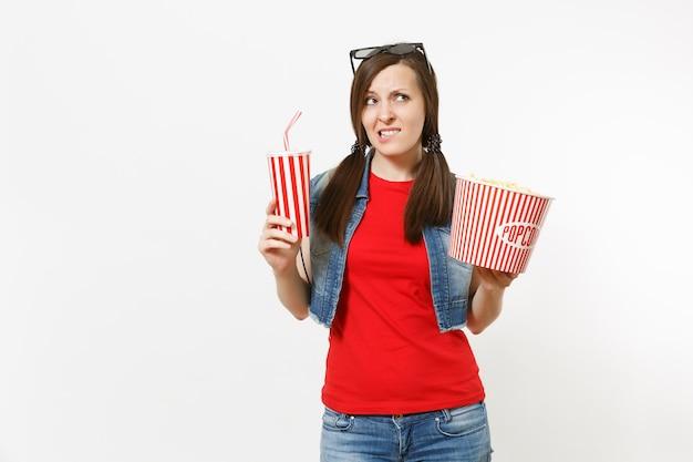 ポップコーンのバケツと白い背景で隔離のソーダまたはコーラのプラスチックカップを保持している映画フィルムを見て唇を噛んで3dimaxメガネで若い心配している女性の肖像画。映画のコンセプトにおける感情。