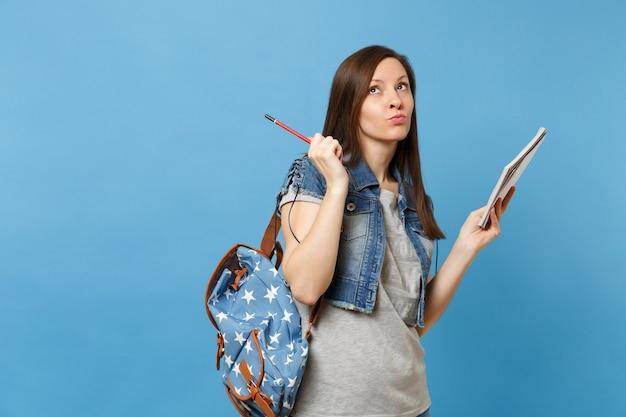 파란색 배경에 격리된 테스트 홀드 노트북 연필에 대해 생각하는 배낭을 메고 데님 옷을 입은 젊은 여성 학생의 초상화. 고등학교 대학 대학에서 교육.