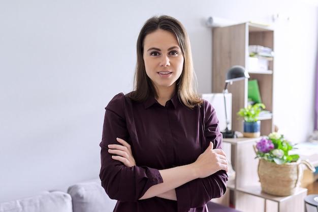 사무실에서 팔짱을 낀 자신감 있는 젊은 여성 정신 사회 치료사의 초상화. 심리학, 심리 치료, 정신 건강, 도움 및 지원 개념
