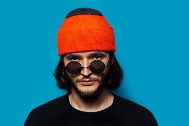 Портрет молодого уверенного парня в солнечных очках, оранжевой шапочке и черном свитере на фоне синего цвета.