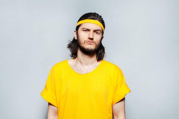 노란색 셔츠에 자신감 젊은이의 초상화입니다.