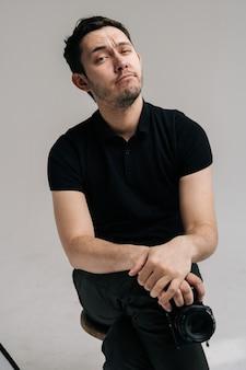 Портрет молодого уверенного фотографа в черной рубашке с цифровой камерой