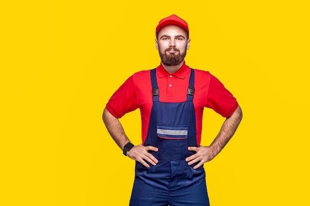 Портрет молодой уверенно ремонтник с бородой в синем комбинезоне, красной футболке и кепке, стоя и держась за руки на талии с улыбкой, закрытый, студийный снимок, изолированный на сером фоне, копией пространства.