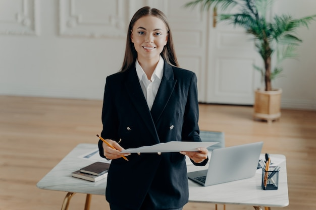Портрет молодой уверенно улыбающейся деловой женщины в черном формальном костюме, держащей документ, с нетерпением ожидая перед белым столом с открытым ноутбуком в офисе с пальмой в горшке на фоне.