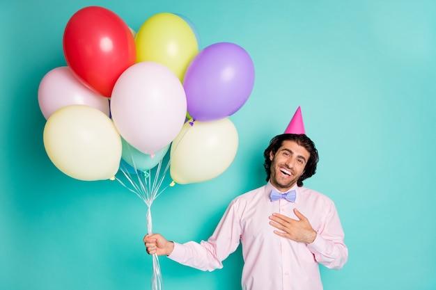 청록색 배경에 격리된 다채로운 풍선을 가져오는 축하하는 젊은 남자의 초상화