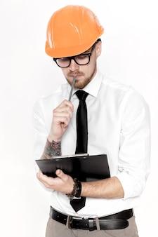 白い背景の上のフォルダーとオレンジ色のヘルメットの若い建設エンジニアの肖像画