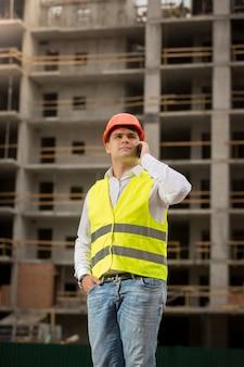 사이트 구축에 전화로 얘기하는 젊은 건설 엔지니어의 초상화
