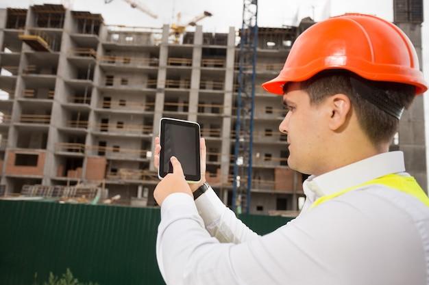 建築現場でデジタルタブレットを使用して若い建設エンジニアの肖像画
