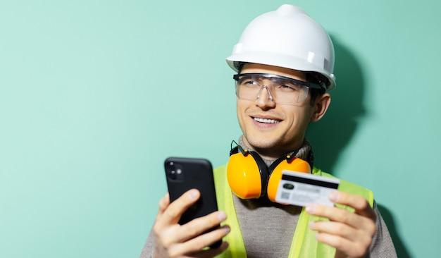 Портрет молодого рабочего инженера-строителя носить оборудование для обеспечения безопасности, используя смартфон и кредитную банковскую карту на фоне цвета морской волны.
