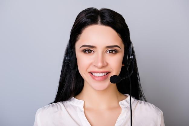 Портрет молодого консультанта call-центра в наушниках, изолированном на сером пространстве