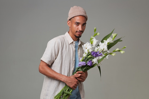 灰色の帽子をかぶった若いクールな魅力的な男の肖像画は、彼の手とポーズで花束を持って、幸せな表情と笑顔でカメラを見て、灰色の背景の上に立っています。